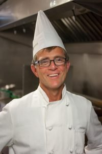 Kerry Beadle smiles as he poses for a photo in the Copper Turret kitchen.